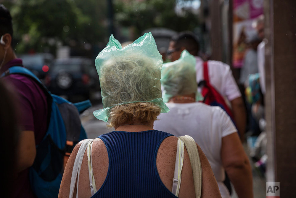 Woman keep their hair dry with plastic bags as it drizzles in downtown Caracas, Venezuela, Tuesday, Oct. 24, 2017. (AP Photo/Rodrigo Abd)
