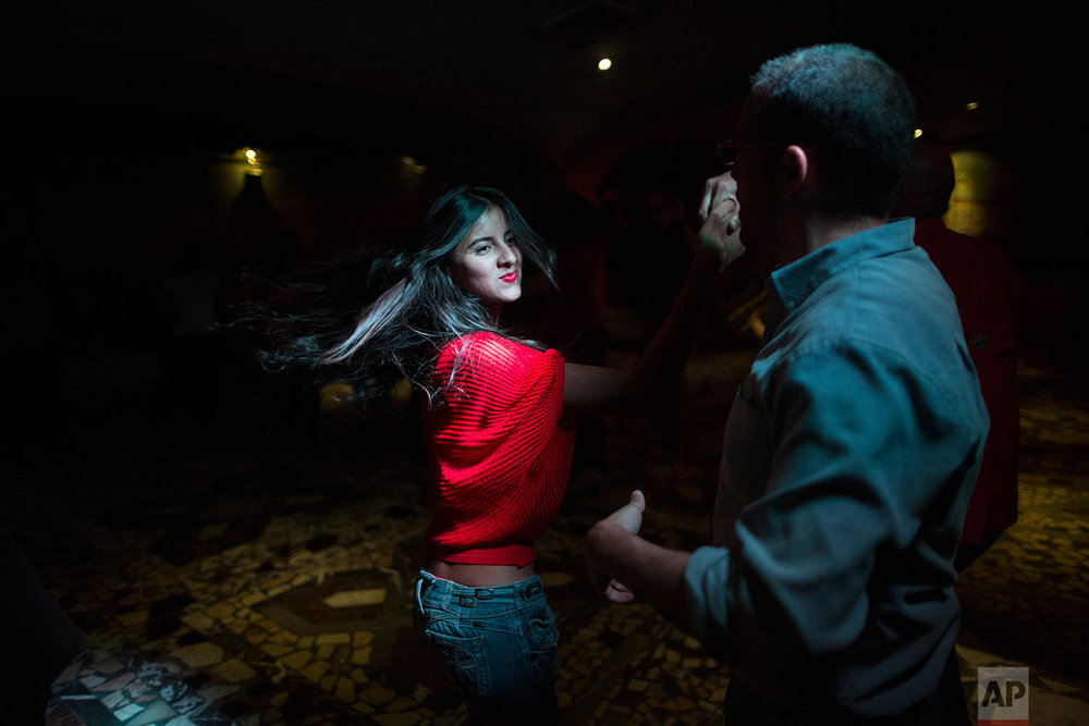 People salsa dance at a club in the financial district of Caracas, Venezuela, Thursday, Oct. 26, 2017. (AP Photo/Rodrigo Abd)