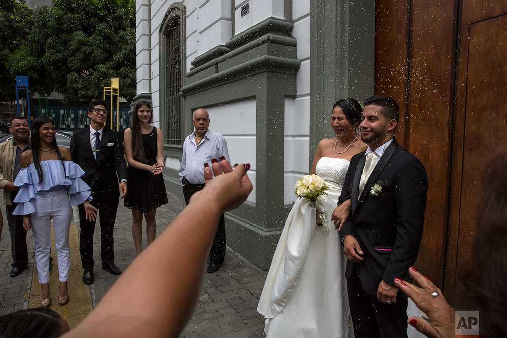 Wedding guests throw rice at Nalitza Perez, 44, and her groom Jason Cifuentes, 26, outside a church in Caracas, Venezuela, Saturday, Oct. 21, 2017. (AP Photo/Rodrigo Abd)