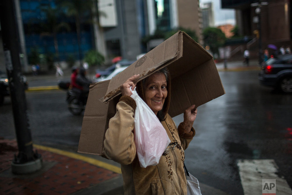 A pedestrian covers herself from the rain with a cardboard box in the financial district of Caracas, Venezuela, Thursday, Oct. 26, 2017. (AP Photo/Rodrigo Abd)
