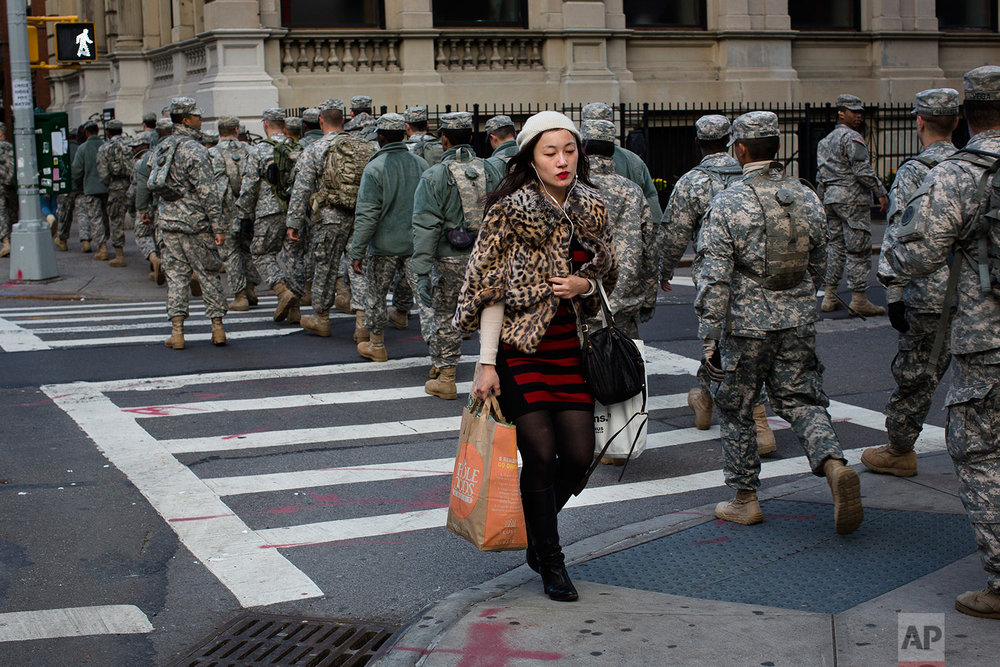 A woman with her groceries passes a group of National Guardsmen as they march up 1st Avenue towards the 69th Regiment Armory, Saturday, Nov. 3, 2012, in New York. National Guardsmen remain in Manhattan as the city begins to move towards normalcy following Superstorm Sandy earlier in the week. (AP Photo/ John Minchillo)