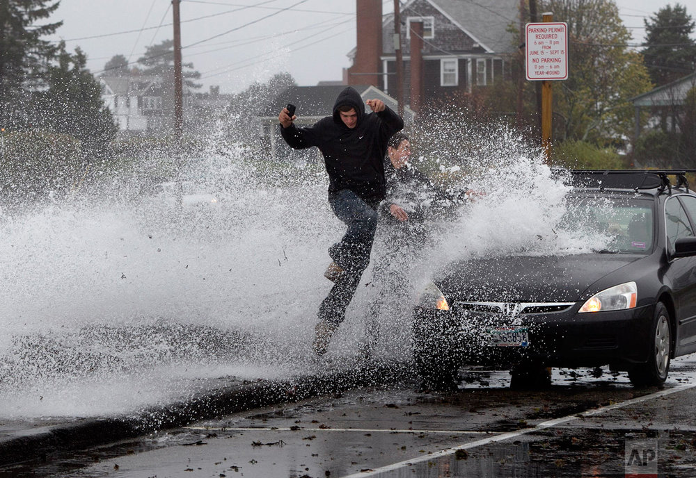 Caleb Lavoie, 17, of Dayton, Maine, front, and Curtis Huard, 16, of Arundel, Maine, leap out of the way as a large wave crashes over a seawall on the Atlantic Ocean during the early stages of Hurricane Sandy, Monday, Oct. 29, 2012, in Kennebunk, Maine. (AP Photo/Robert F. Bukaty)
