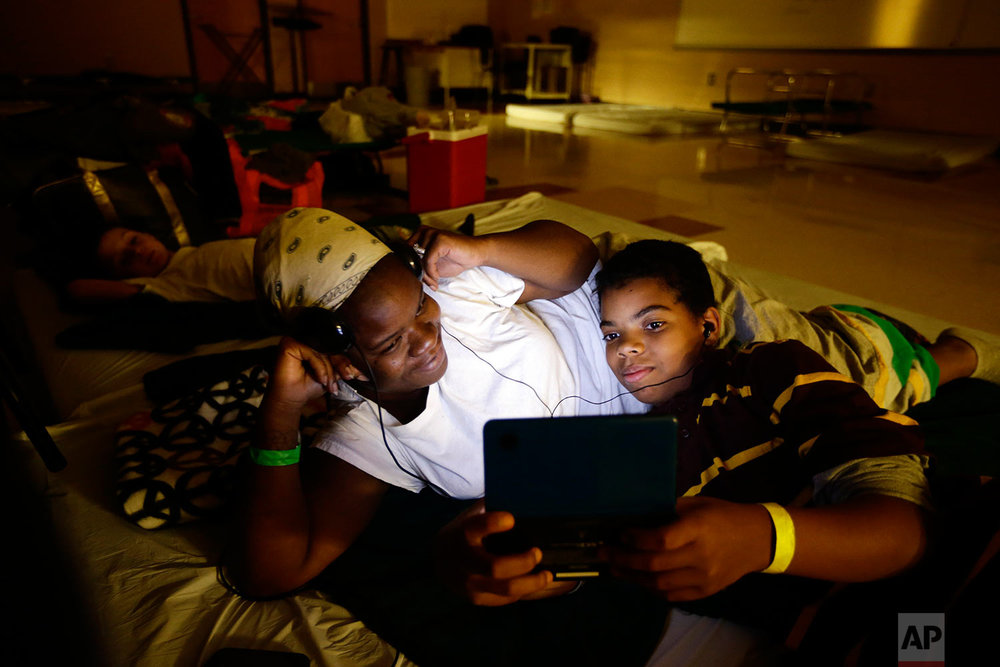 In this Oct. 30, 2012 photo, Crystal Medley, left, and her son Christian Jackson 11, play a video game at a shelter at Washington High School, in the aftermath of Superstorm Sandy in Princess Anne, Md. (AP Photo/Alex Brandon)