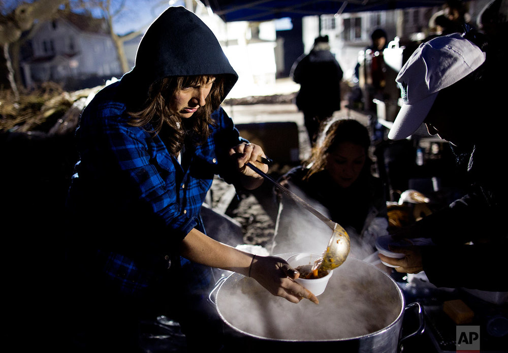 Ariel Nadelberg of the Brooklyn borough of New York pours hot soup in a cup at a parking lot that has become make shift place where those in need can get food and clothing in a Rockaway neighborhood of the borough of Queens, New York, Monday, Nov. 5, 2012, as efforts to bring goods and services to people goes on in the wake of Superstorm Sandy. Many volunteers have shown up on their own to try to lend a hand any way they can. (AP Photo/Craig Ruttle)