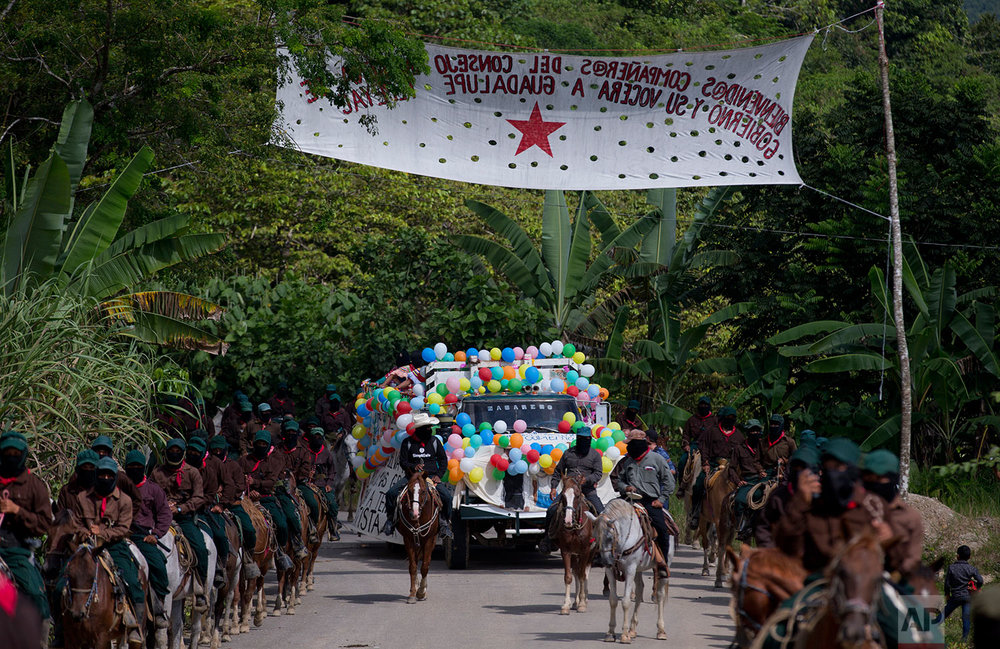 In this Saturday, Oct. 14, 2017 photo, horse riding members of the Zapatista National Liberation Army (EZLN) escort Maria de Jesus Patricio, presidential candidate for the National Indigenous Congress, as she campaigns in the Zapatista stronghold of Guadalupe Tepeyac, in the southern state of Chiapas, Mexico. (AP Photo/Eduardo Verdugo)