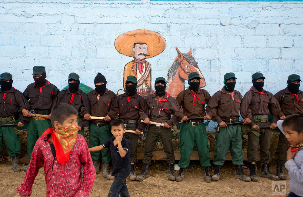 In this Monday, Oct. 16, 2017 photo, members of the Zapatista National Liberation Army (EZLN) provide security for a campaign rally by presidential candidate for the National Indigenous Congress, Maria de Jesus Patricio, in the Zapatista stronghold of La Garrucha in the southern state of Chiapas, Mexico. The mural features Mexican revolutionary leader Emiliano Zapata. (AP Photo/Eduardo Verdugo)