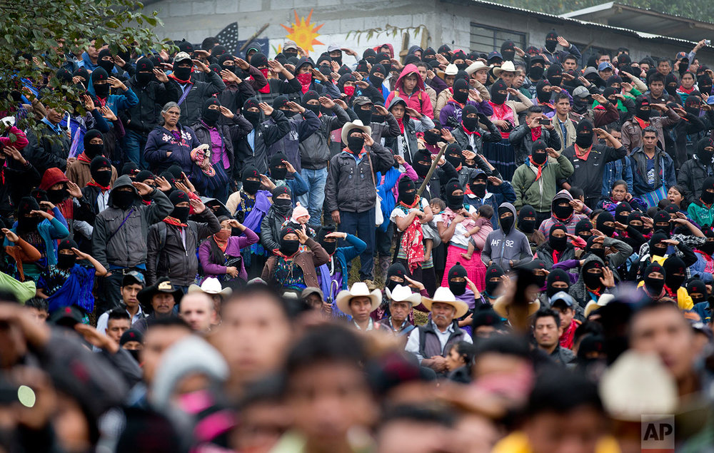 In this Thursday, Oct. 19, 2017 photo, Zapatistas salute during the playing of Mexico's national anthem at a campaign rally for Maria de Jesus Patricio, presidential candidate for the National Indigenous Congress, in the Zapatista stronghold of Oventic in the southern state of Chiapas, Mexico. Patricio is unlikely to win the presidency, or even get on the ballot, but her campaign has nonetheless generated an unusual amount of enthusiasm. (AP Photo/Eduardo Verdugo)