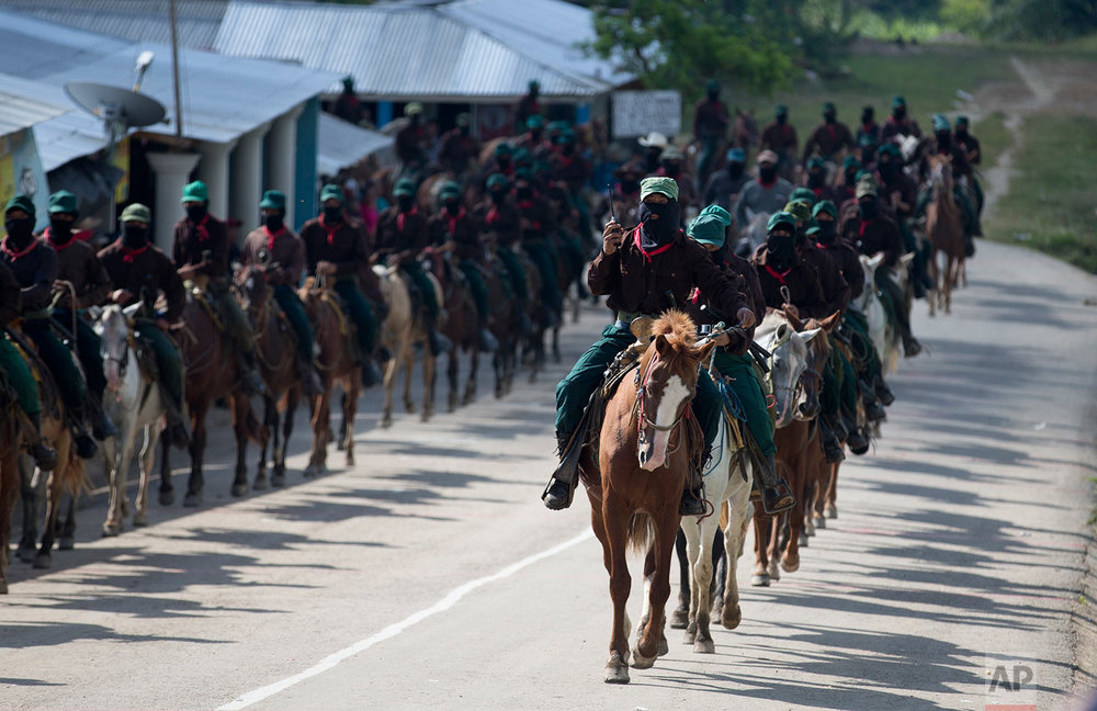 In this Saturday, Oct. 14, 2017 photo, members of the Zapatista National Liberation Army (EZLN) arrive on horseback to escort Maria de Jesus Patricio, presidential candidate for the National Indigenous Congress, campaigning in the Zapatista stronghold of Guadalupe Tepeyac in the southern state of Chiapas, Mexico. Patricio, who has no electoral machine and was essentially unknown until she was named the candidate for the National Indigenous Congress in May, gathered 4,734 signatures, more than a major state governor, a former legislator and 44 others trying to get on the ballot. (AP Photo/Eduardo Verdugo)