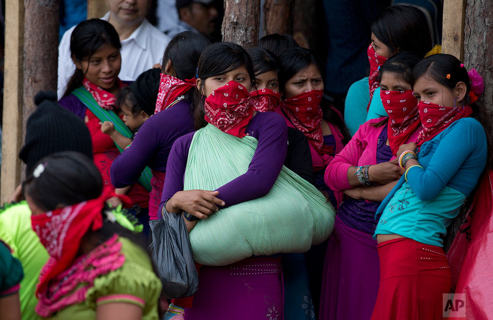"In this Saturday, Oct. 14, 2017 photo, masked indigenous women, one holding a child in a sling, wait for Maria de Jesus Patricio, presidential candidate for the National Indigenous Congress, to arrive at a campaign rally in the Zapatista stronghold of Guadalupe Tepeyac in the southern state of Chiapas, Mexico. ""Now is the time to look toward our communities, and look toward our brothers,"" Patricio said at the rally. ""What we are suffering, they are suffering, too, even if they are of a different color or think differently than we do."" (AP Photo/Eduardo Verdugo)"