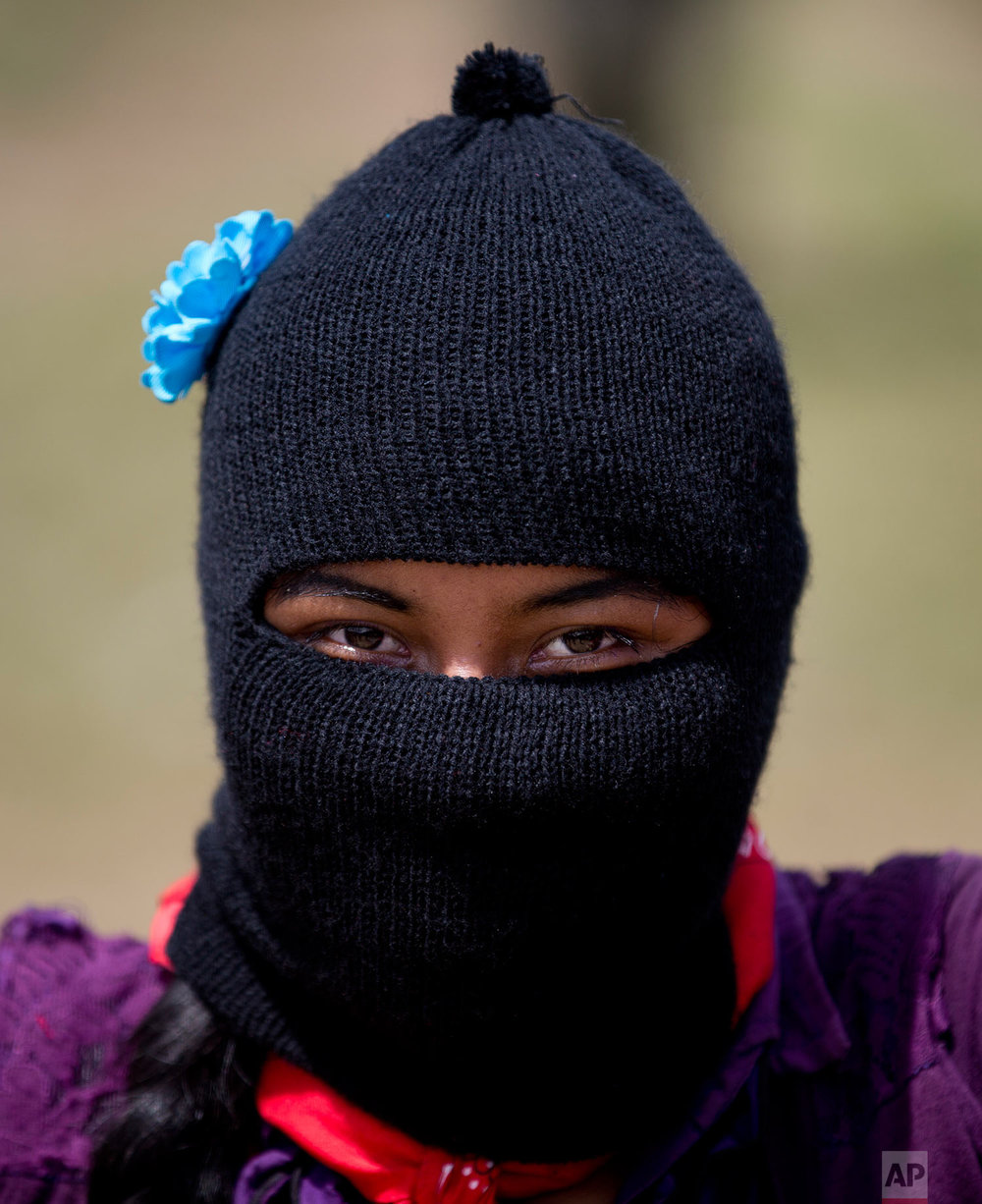 In this Saturday, Oct. 14, 2017 photo, a young woman wearing a mask decorated with a blue flower waits for the arrival of Maria de Jesus Patricio, presidential candidate for the National Indigenous Congress, at a campaign rally in the Zapatista stronghold of Guadalupe Tepeyac in the southern state of Chiapas, Mexico. (AP Photo/Eduardo Verdugo)