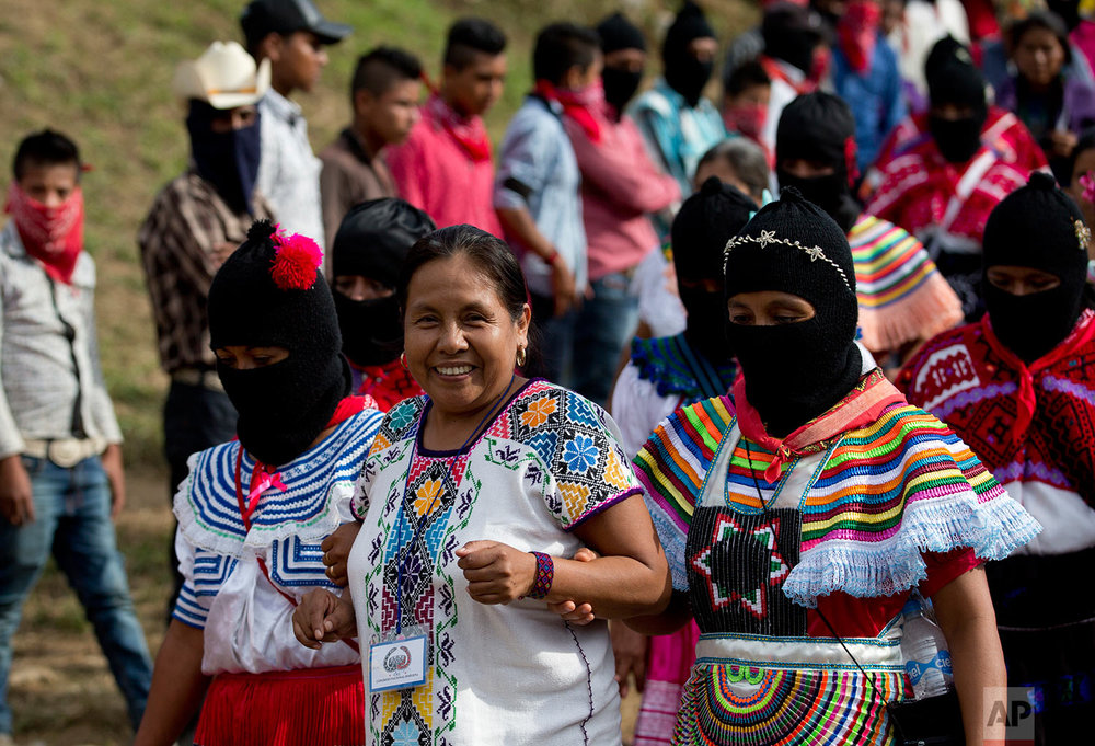 In this Saturday, Oct. 14, 2017 photo, masked women escort Maria de Jesus Patricio, presidential candidate for the National Indigenous Congress, as she campaigns in the Zapatista stronghold of Guadalupe Tepeyac in the southern state of Chiapas, Mexico. Patricio has never worn a power suit or heels, but rather always appears in an embroidered indigenous blouse and pants or skirt. (AP Photo/Eduardo Verdugo)