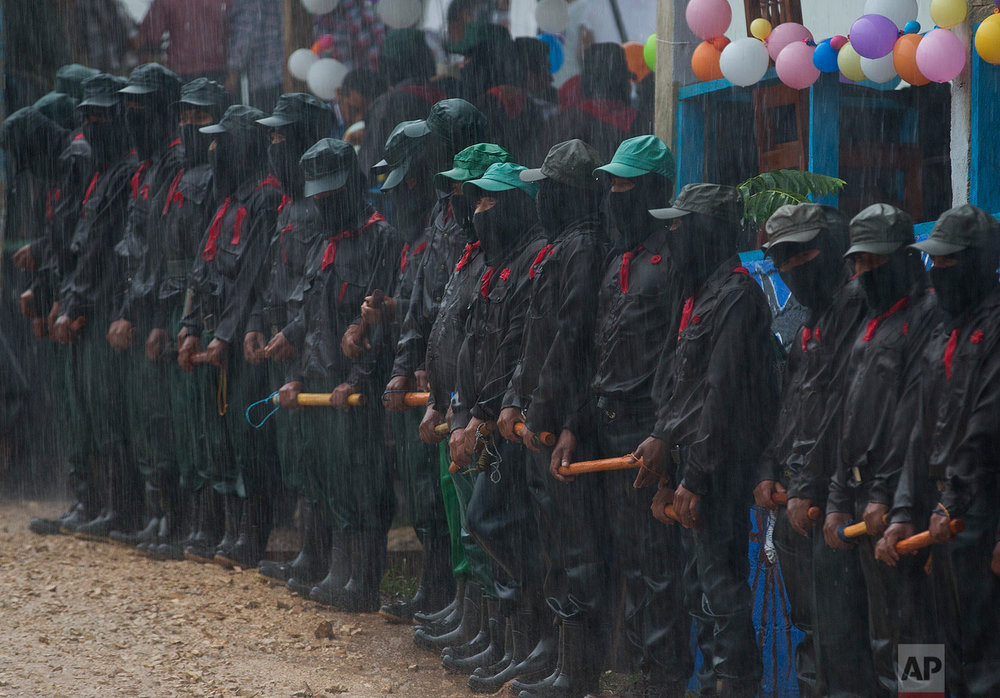 In this Monday, Oct. 16, 2017 photo, members of the Zapatista National Liberation Army (EZLN) stand in the pouring rain as they provide security during a campaign rally for Maria de Jesus Patricio, presidential candidate for the National Indigenous Congress, in the Zapatista stronghold of La Garrucha in the southern state of Chiapas, Mexico. The Zapatistas staged a brief armed uprising in 1994 for greater indigenous rights. (AP Photo/Eduardo Verdugo)