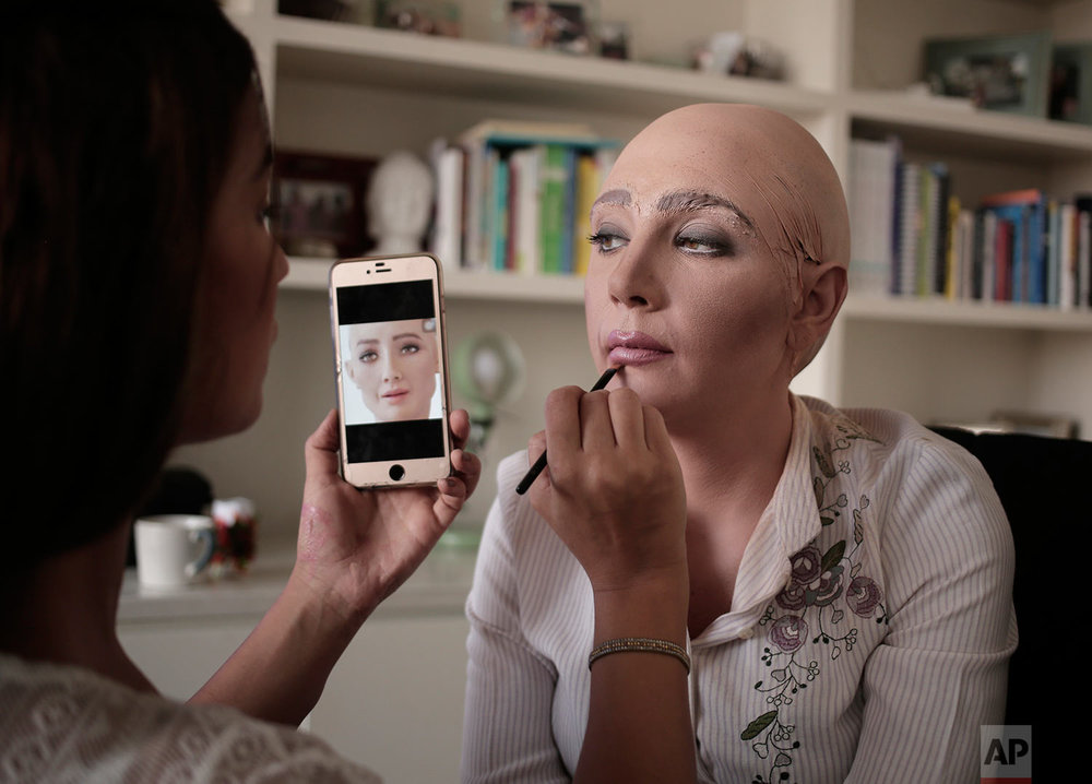 Egyptian satirist Sherine Arafa gets her make-up done for halloween as 'Sophia the Robot,' who has recently been declared a citizen of the Kingdom of Saudi Arabia, at her home, in Cairo, Egypt, Tuesday, Oct. 31, 2017.  (AP Photo/Nariman El-Mofty)