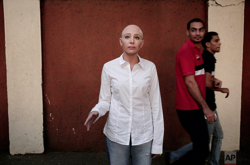 Egyptian satirist Sherine Arafa dressed up for halloween as 'Sophia the Robot,' who has recently been declared a citizen of the Kingdom of Saudi Arabia, poses for a photo as men look at her on a street, in Cairo, Egypt, Tuesday, Oct. 31, 2017. (AP Photo/Nariman El-Mofty)