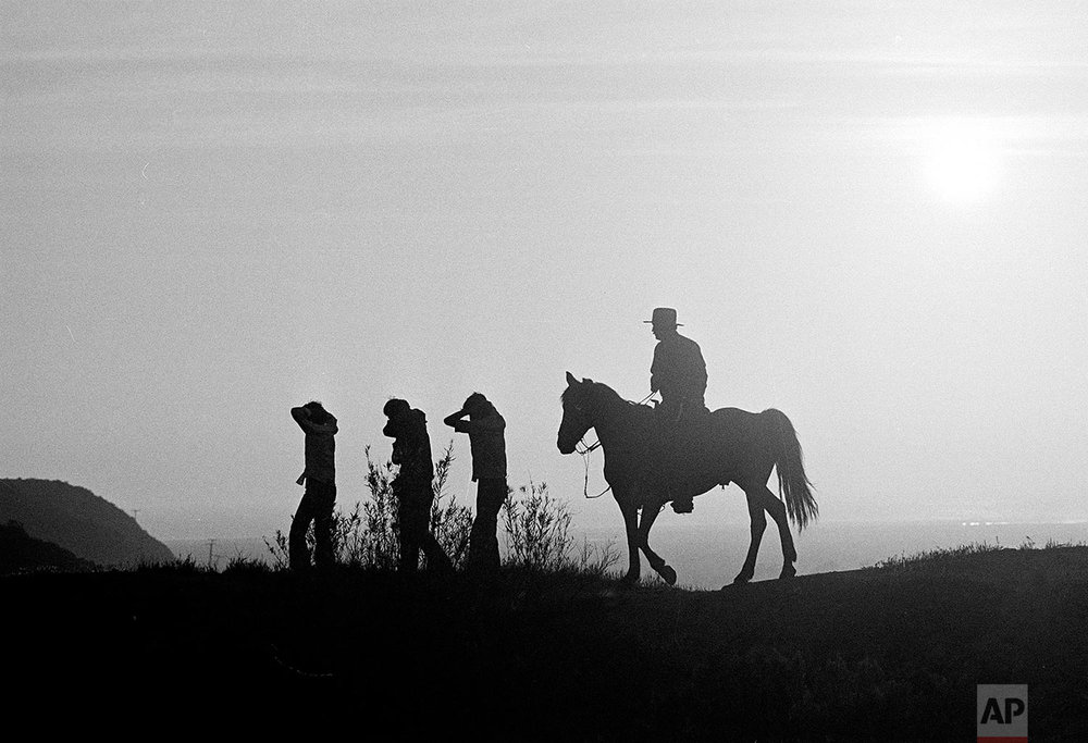 In this Aug. 18, 1981, photo taken by Associated Press photographer Lennox McLendon, shows U.S. Border Patrol officer Ed Pyeatt, on horseback, leading a group of immigrants who crossed the border without legal permission, down the hillside toward waiting vans for the trip to a holding center at the Chula Vista, Calif., border station. (AP Photo/Lennox McLendon)