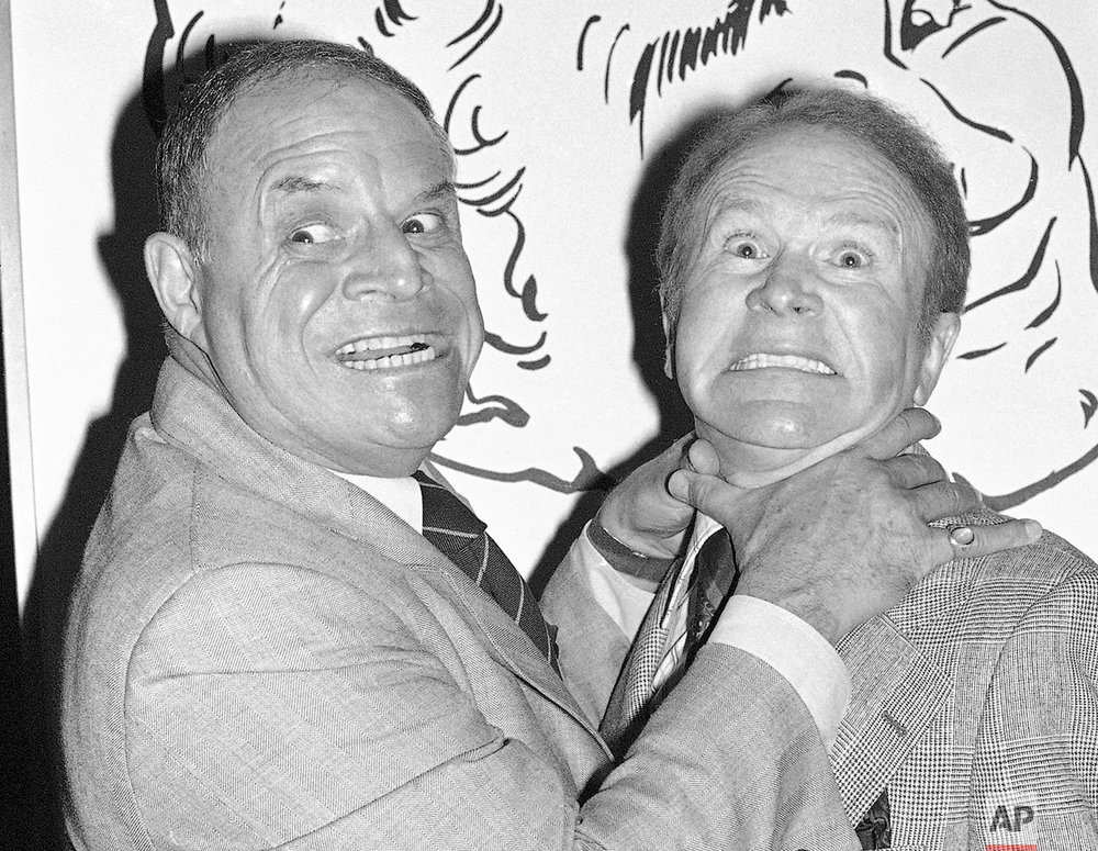 In this Nov. 10, 1977 photo, taken by Associated Press photographer Lennox McLendon shows comedians Don Rickles, left, pretending to strangle Red Buttons prior to an Annual Stag Roast in Los Angeles. AP Photo/ Lennox McLendon)