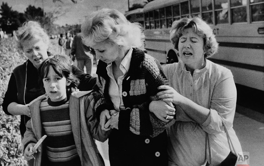 Unidentified women greet a young boy who was evacuated by bus to a nearby junior high school in San Diego from the schoolyard of the Cleveland Elementary School after a sniper opened fire on the schoolyard, Jan. 29, 1979. (AP Photo/Lennox McLendon)