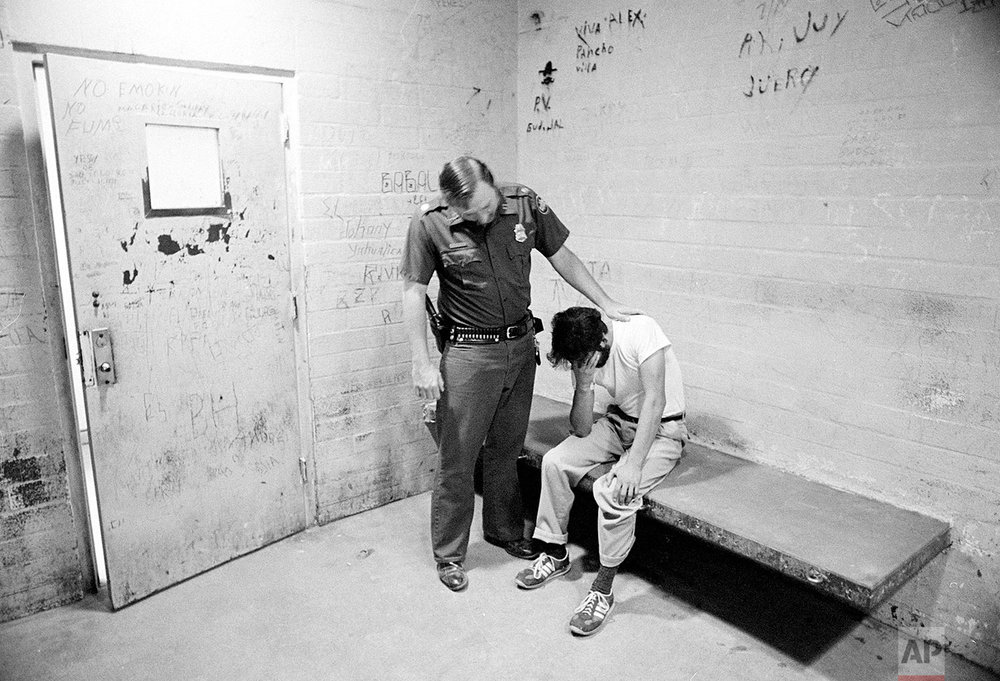 "U.S. Border Patrol officer Ed Pyeatt consoles an unidentified illegal immigrant sitting in a cell at Chula Vista station, a border town to Mexico, August 18, 1981. ""With a government that doesn't care for them, indecent living conditions and poverty, you can't blame them."" says Pyeatt. (AP Photo/Lennox McLendon)"