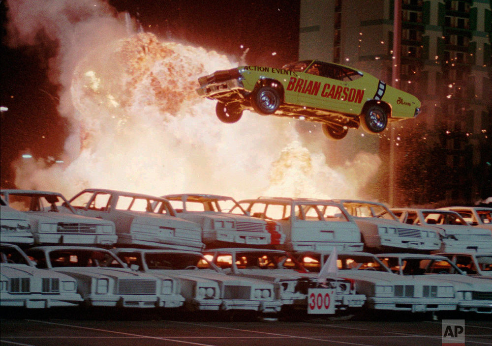 "In this Feb. 11, 1998, photo, taken by Associated Press photographer Lennox McLendon, shows Internationally known stunt driver Brian Carson of Tarzana, Calif., crossing over the 300-foot marker as he sets a new ""auto flight"" world record at the Orleans Hotel and Casino in Las Vegas. Carson shattered his own 298-foot world record with a flight of 314 feet at a speed of 93 mph. (AP Photo/Lennox McLendon)"