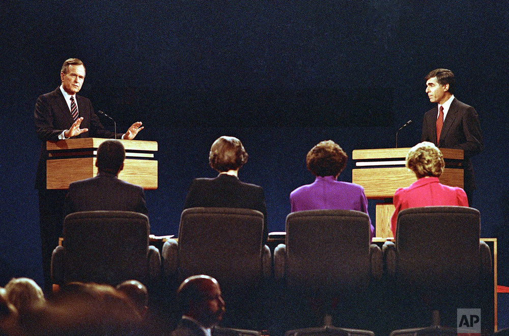 Vice President George Bush (left) gestures while making a point to the panel as Gov. Michael Dukakis watches at right during the second presidential debate on Thursday, Oct. 13, 1988 in Los Angeles. (AP Photo/Lennox McLendon)