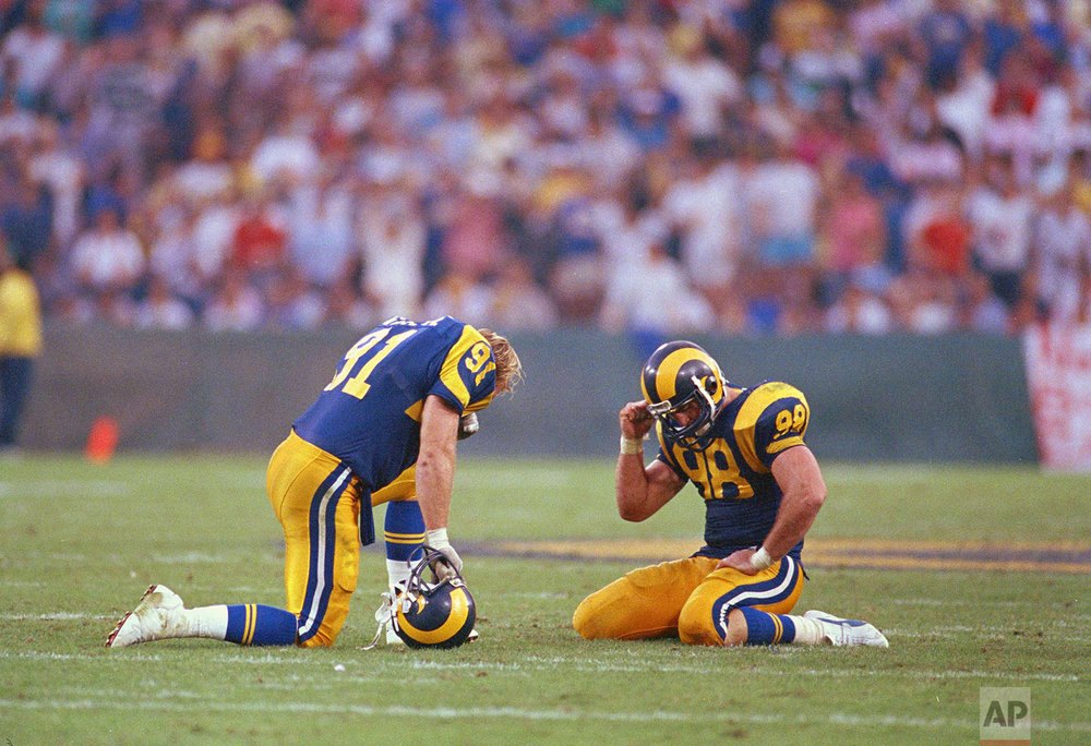 Los Angeles Rams defenders Kevin Greene, left, and Shawn Miller react after the New England Patriots quarterback Tony Eason threw a desperation pass in the end zone with time running out to defeat the Rams 30-28, Nov. 16, 1986, in Anaheim. Patriots wide receiver Irving Fryar caught the deflected ball for the win. (AP Photo/Lennox McLendon)