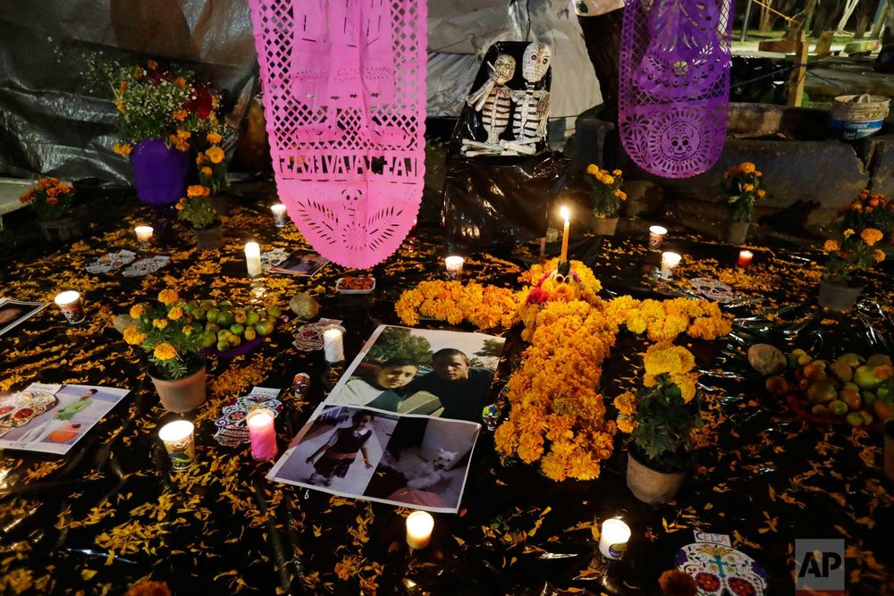 Pictures of Julian Flores, 11, and his little sister Ximena, 6, lie amidst flowers and candles in a Day of the Dead altar erected in a tent camp outside Mulitfamiliar Tlalpan, where nine people including Nayeli Flores' two children were killed when a building collapsed in the Sept. 19 earthquake, in Mexico City, Tuesday, Oct. 31, 2017. (AP Photo/Rebecca Blackwell)