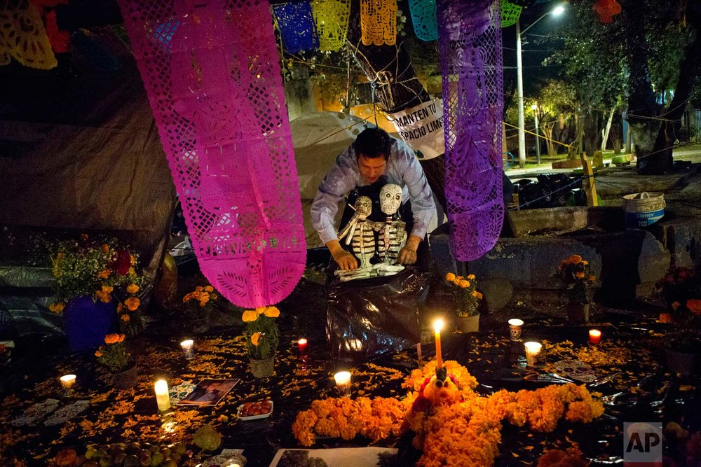 A young man arranges skeletons on a Day of the Dead altar at a tent encampment at Multifamiliar Tlalpan, where nine people died when a building collapsed in the Sept. earthquake, in Mexico City, Tuesday, Oct. 31, 2017. People in Mexico are marking this year's holiday by remembering the people killed in the Sept. 19 earthquake. (AP Photo/Rebecca Blackwell)
