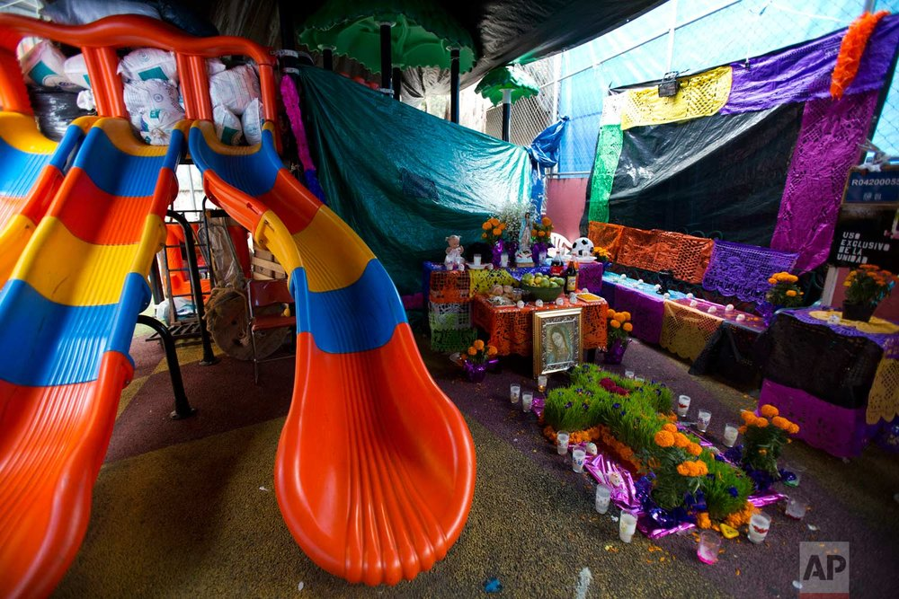 A Day of the Dead altar is set up next to playground equipment under a tent encampment at Multifamiliar Tlalpan, where nine people died when a building collapsed in the Sept. 19 earthquake, in Mexico City, Tuesday, Oct. 31, 2017. Mexico's traditional Day of the Dead is opening with a sadder tone than usual Wednesday. (AP Photo/Rebecca Blackwell)