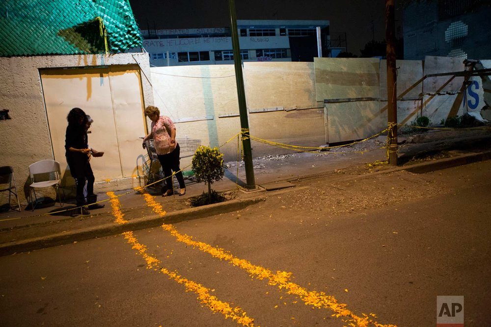 Neighbors of the Enrique Rebsamen school, part of which collapsed in the Sept. 19 earthquake, make a trail of marigold petals from the school entrance to an altar where they have placed toys, food, sugar skulls, and flowers for the dead, in Mexico City, late Tuesday, Oct. 31, 2017. The trail was meant to provide a symbolic path for the spirits of the more than 20 children who died there to reach the altar on the night of Day of the Dead celebrations when children are remembered. (AP Photo/Rebecca Blackwell)