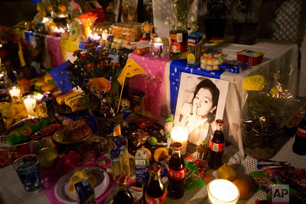 """An photograph of Alexandra Arias, 11, is surrounded by food, flowers, and candles in a Day of the Dead altar set up in front of the Enrique Rebsamen school, part of which collapsed in the Sept. 19 earthquake, killing more than two dozen people, mostly children, in Mexico City, Tuesday, Oct. 31, 2017. Mexico's traditional view of the dead is not ghoulish or frightful, rather they are seen as the """"dear departed,"""" but this time many of the dead departed so recently that the grief is still fresh. (AP Photo/Rebecca Blackwell)"""
