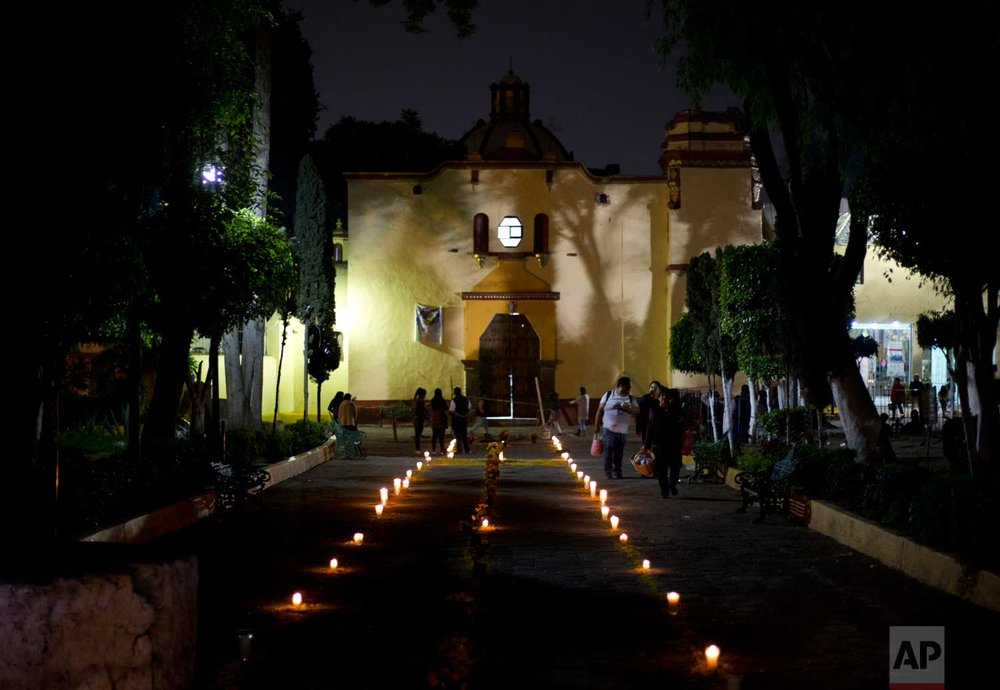 A path made of candles and marigold flowers lead to the main church in San Gregorio Atlapulco, Mexico where a Day of the Dead altar honors two people who died when the church dome fell during the earthquake, late Tuesday, Oct. 31, 2017. People in Mexico are marking this year's holiday by remembering the people killed in the Sept. 19 earthquake. (AP Photo/Eduardo Verdugo)