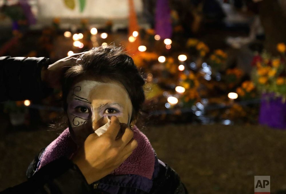A girl gets her Day of the Dead makeup wiped off beside an altar inside a tent encampment at Multifamiliar Tlalpan, where nine people died when a building collapsed in the Sept. earthquake, in Mexico City, Tuesday, Oct. 31, 2017. People in Mexico are marking this year's holiday by remembering the people killed in the Sept. 19 earthquake. (AP Photo/Rebecca Blackwell)