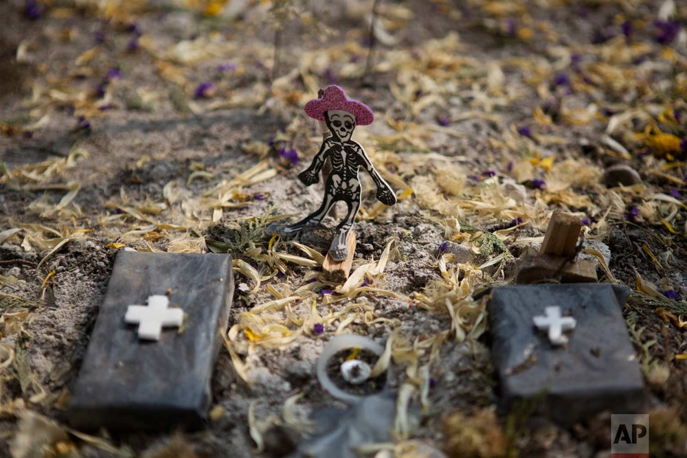 """A skeleton figure stands in a miniature cemetery, part of a small Day of the Dead altar across the street from the remains of Alvaro Obregon 286, where dozens of people were killed when the seven-story office building collapsed in the Sept. earthquake, in Mexico City, Tuesday, Oct. 31, 2017. Mexico's traditional view of the dead is not ghoulish or frightful, rather they are seen as the """"dear departed,"""" but this time many of the dead departed so recently that the grief is still fresh. (AP Photo/Rebecca Blackwell)"""