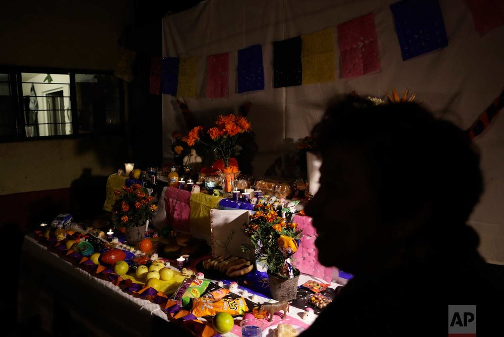 A woman stands beside a Day of the Dead altar outside the Enrique Rebsamen school, part of which collapsed in the Sept. earthquake killing more than two dozen people, mostly children, in Mexico City, Tuesday, Oct. 31, 2017. People in Mexico are marking this year's holiday by remembering the people killed in the Sept. 19 earthquake. (AP Photo/Rebecca Blackwell)