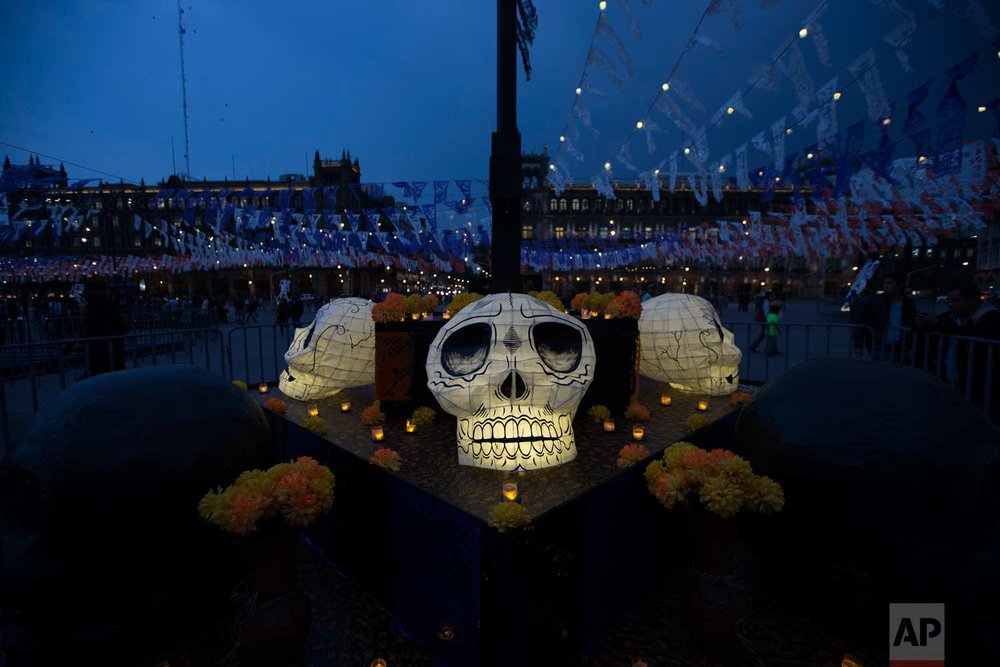 An altar in honor of the dead stands in the Zocalo, as part of Day of the Dead festivities in Mexico City, late Monday, Oct. 30, 2017. The capital's main plaza is filled with shrines dedicated to those killed in two recent earthquakes, ahead of the Nov. 2 holiday. (AP Photo/Moises Castillo)