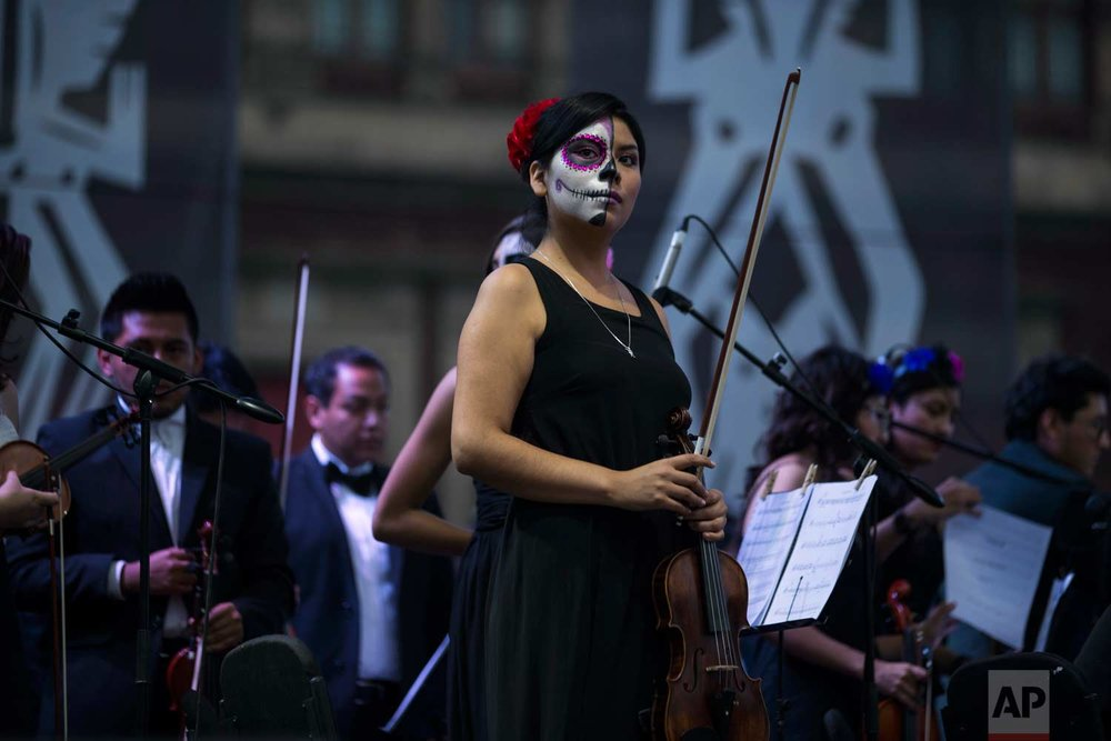 """A musician from the Mexico City Philharmonic Orchestra, with her face painting as """"Catrina,"""" acknowledges the crowd between songs during Day of the Dead festivities in the Zocalo of Mexico City, late Monday, Oct. 30, 2017. The capital's main plaza is filled with shrines dedicated to those killed in two recent earthquakes, ahead of the Nov. 2 holiday. (AP Photo/Moises Castillo)"""