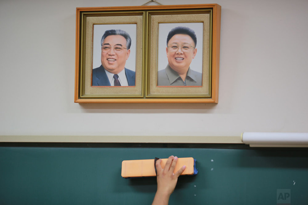 In this Sept. 26, 2017 photo, a student cleans the blackboard under the portraits of the late North Korean leaders Kim Il Sung and Kim Jong Il hanging on the classroom wall at a Tokyo Korean high school in Tokyo. (AP Photo/Eugene Hoshiko)