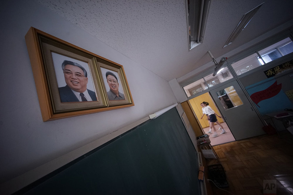 In this Sept. 26, 2017, photo, students walk by a classroom where the portraits of the late North Korean leaders Kim Il Sung and Kim Jong Il hang on the wall at a Tokyo Korean junior and senior high school in Tokyo.  (AP Photo/Eugene Hoshiko)