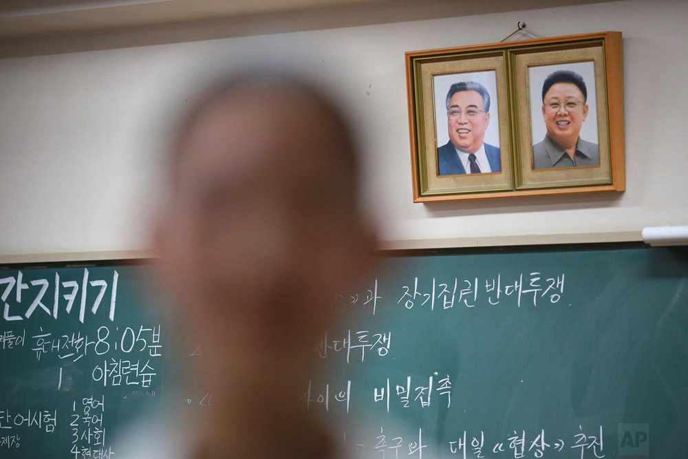 In this Sept. 26, 2017, photo, a student stands near the portraits of the late North Korean leaders Kim Il Sung and Kim Jong Il hanging on a classroom wall in a Korean high school in Tokyo. Many third- and fourth-generation descendants of Koreans brought to Japan during the imperialist years before and during World War II remain loyal to their roots. (AP Photo/Eugene Hoshiko)