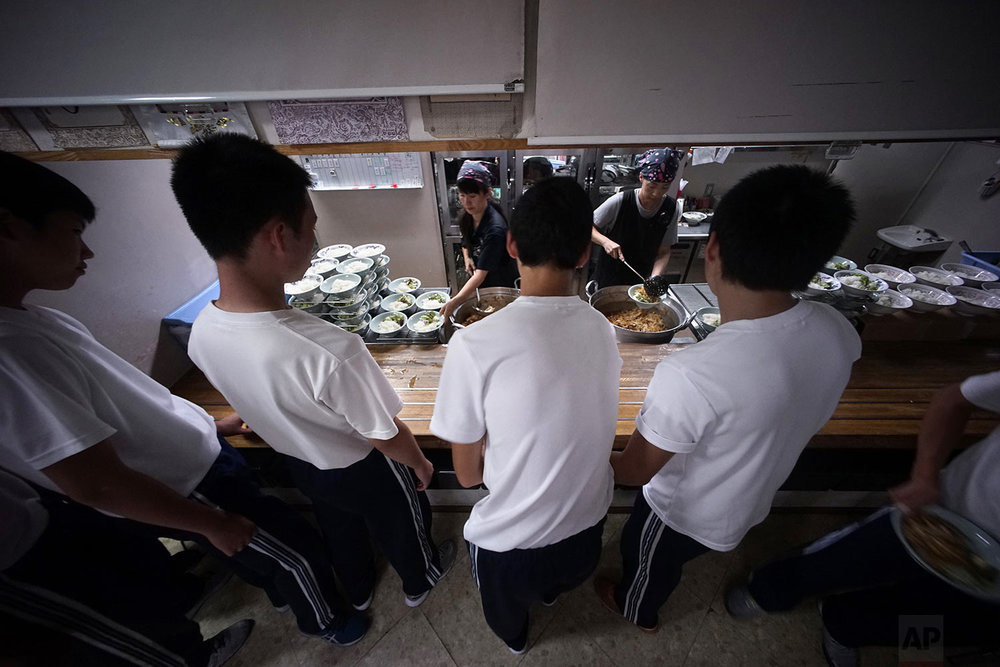 In this Sept. 26, 2017, photo, students line up for lunch at a dining hall in a Korean high school in Tokyo. (AP Photo/Eugene Hoshiko)
