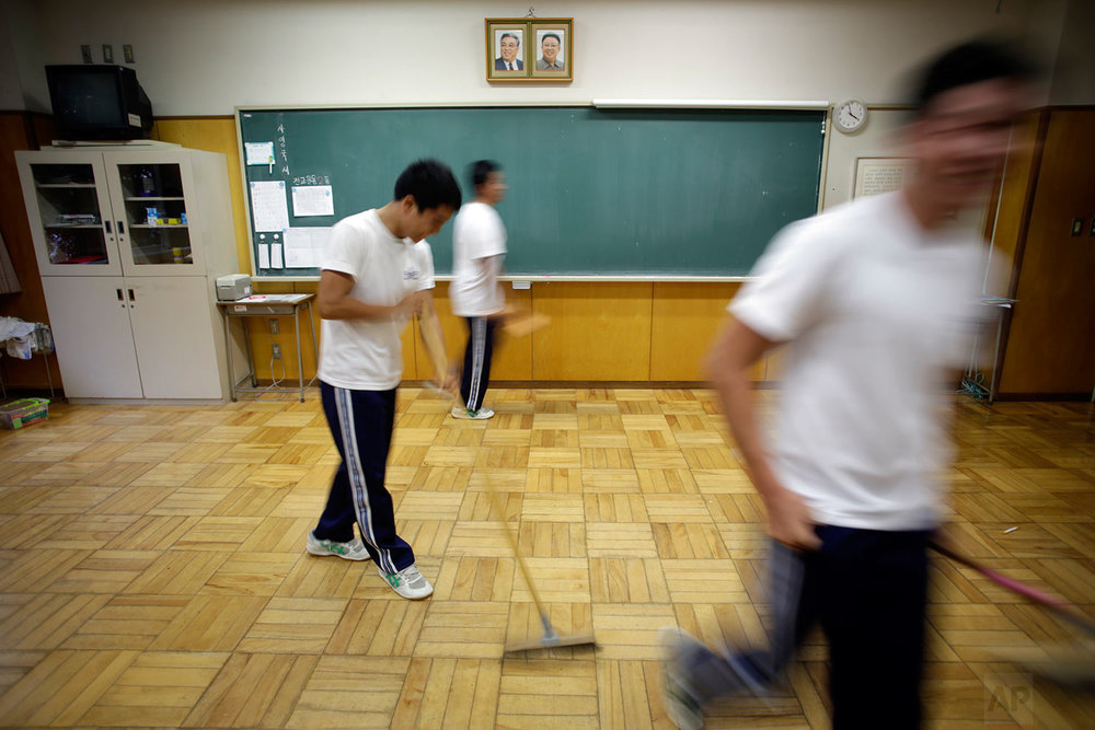 In this Sept. 26, 2017, photo, students clean their classroom under portraits of the late North Korean leaders Kim Il Sung and Kim Jong Il at a Korean high school in Tokyo. (AP Photo/Eugene Hoshiko)
