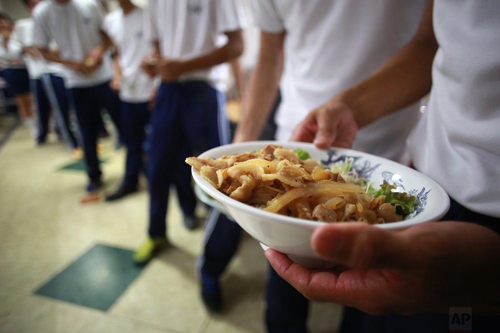 In this Sept. 26, 2017, photo, students line for lunch at a dining hall at a Korean high school in Tokyo. (AP Photo/Eugene Hoshiko)
