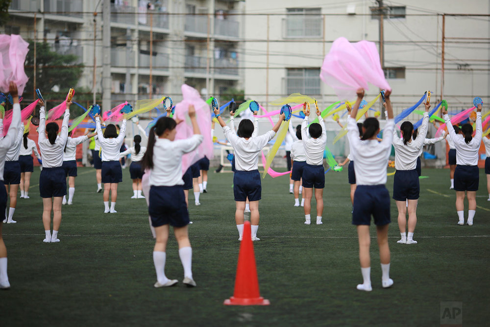 In this Sept. 26, 2017, photo, students practice flag cheering routines at a Korean high school in Tokyo. Many third- and fourth-generation descendants of Koreans brought to Japan during the imperialist years before and during World War II remain loyal to their roots. Families send children to private schools that favor North Korea and teach the language, culture and history of their ancestry. Despite North Korean missile launches and nuclear tests, students say they take pride and view their community as a haven from discrimination by ethnic Japanese.(AP Photo/Eugene Hoshiko)