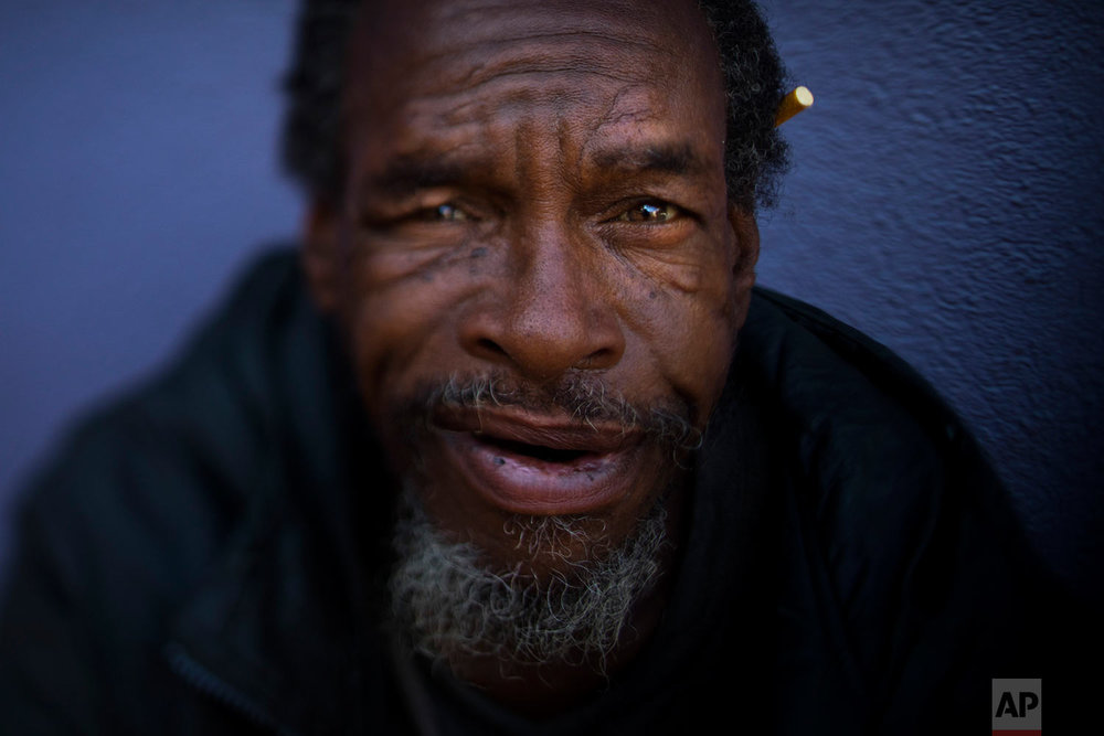 "Moi Williams, 59, Wednesday, Sept. 13, 2017, in Los Angeles. Williams, who has been homeless for four years, said he is comfortable sleeping on the street. ""I'm not bothering nobody. I'm not being bothered."" The homeless are easy to pass by on the street. It's harder when you look into their eyes. Their gazes hint at lost promise or a glimmer of hope. Some are sad, some placid, others haunting. Behind each person is a story that however vague offers some glimpse into their lives. (AP Photo/Jae C. Hong)"