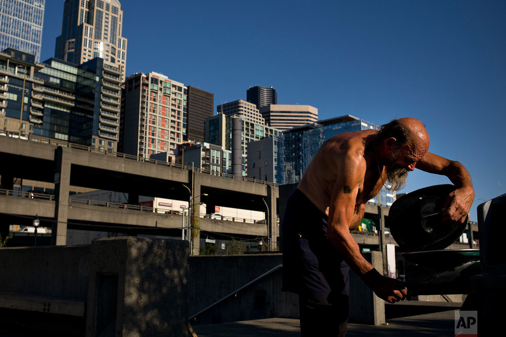 Joseph Nalty, a 64-year-old homeless man who grew up in Iowa, dampens his hat to cool off in the Waterfront Park area of Seattle on Thursday, Sept. 28, 2017. A homeless crisis of unprecedented proportions is rocking the West Coast, and its victims are being left behind by the very things that mark the region's success: soaring housing costs, rock-bottom vacancy rates and a roaring economy that waits for no one. (AP Photo/Jae C. Hong)