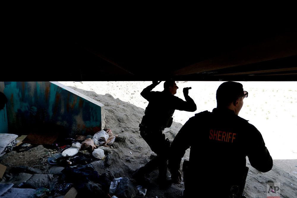 Officers from the Oranges County Sheriffs Dept. patrol a homeless encampment along the Santa Ana River Friday, Sept. 22, 2017, in Anaheim, Calif. Anaheim is the latest California city to declare a state of emergency because of a growing homeless crisis. (AP Photo/Chris Carlson)
