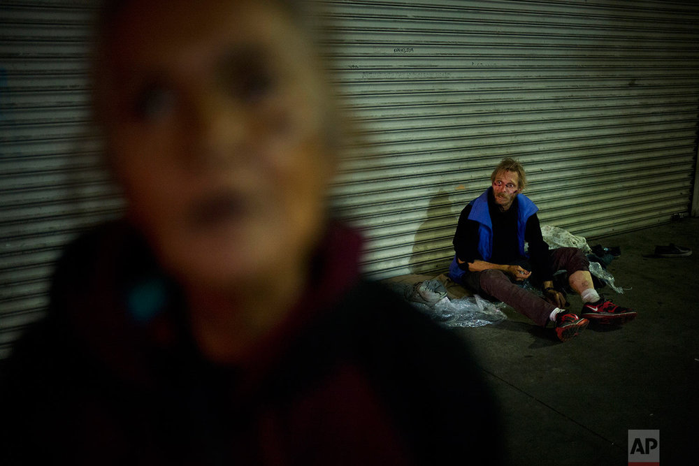 A mentally disabled woman stares at a camera as a homeless drug addict, who said his name was April Jane, sits on a sidewalk asking for money, Thursday, Nov. 2, 2017, in downtown Los Angeles. The latest nationwide homeless count shows that 4 of every 10 people living on the street are severely mentally ill or have a serious drug addiction. (AP Photo/Jae C. Hong)