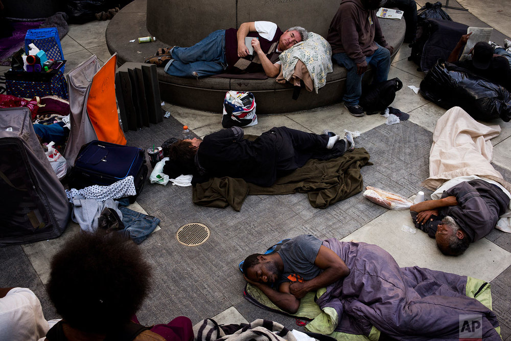 A group of homeless people sleep in the courtyard of the Midnight Mission Thursday, Sept. 14, 2017, in Los Angeles. The mission's courtyard is open to any homeless people looking for a safe place to spend the night. A homeless crisis of unprecedented proportions is rocking the West Coast, and its victims are being left behind by the very things that mark the region's success: soaring housing costs, rock-bottom vacancy rates and a roaring economy that waits for no one. (AP Photo/Jae C. Hong)