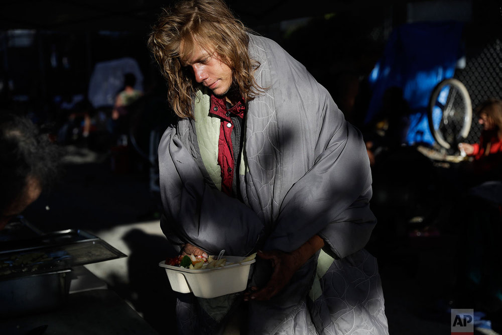 A man gets a meal from Food not Bombs, an advocacy group helping homeless people, Sunday, Oct. 1, 2017, in Santa Cruz, Calif. On a street corner in Santa Cruz's main thoroughfare, the organization sets up a meal station on Saturdays and Sundays for the city's increasing homeless population, despite constant pressure from some residents in the downtown district. (AP Photo/Marcio Jose Sanchez)