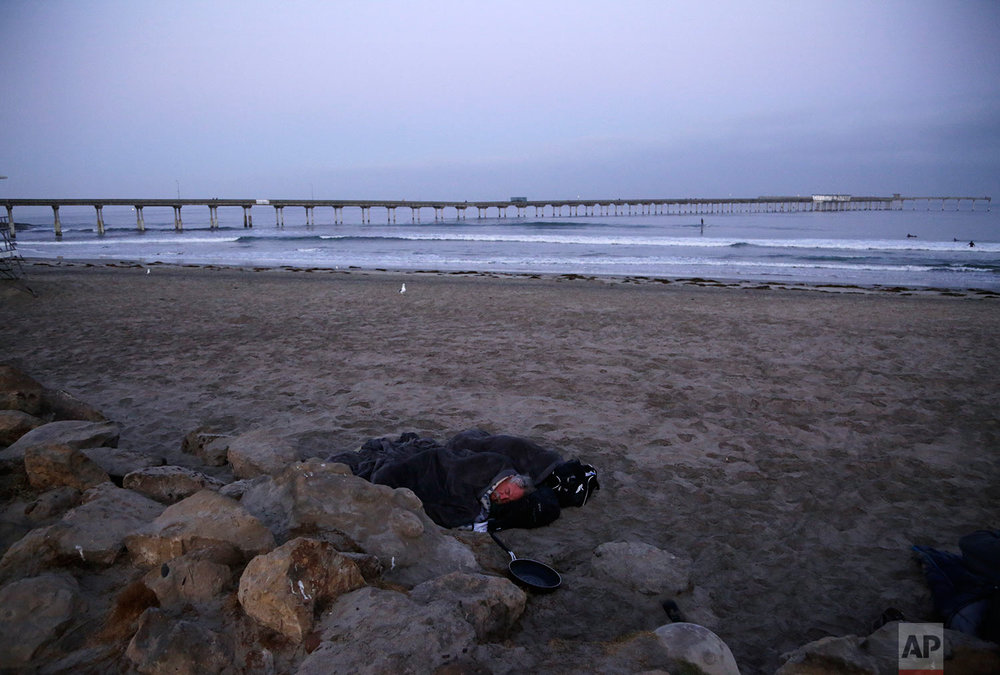 A person sleeps under a blanket on a beach near the Ocean Beach Pier in San Diego on Sept. 28, 2017. A homeless crisis of unprecedented proportions is rocking the West Coast, leaving elected officials and outreach workers scrambling for solutions. (AP Photo/Gregory Bull)